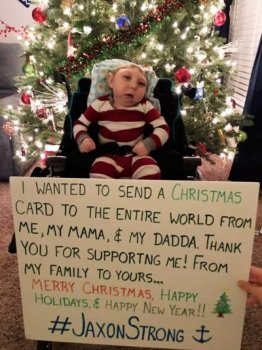 Father Brandon Buell posted this photo of son Jaxon, who was born with only part of his skull and brain, in front of a Christmas card to the world.