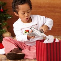 little boy opening airplane present
