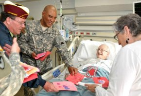 Male Veteran in inpatient care receiving Valentines cards from volunteers and visitors